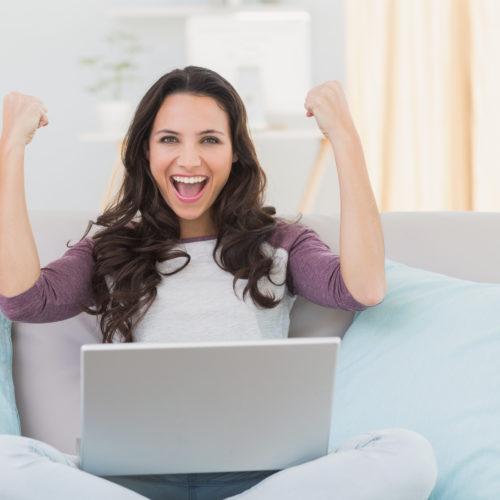 vrouw juichend achter laptop
