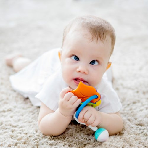 Baby met oogaandoening speelt met rammelaar