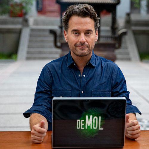 Presentatotor 'Wie is de mol?' achter laptop met logo WIDM.