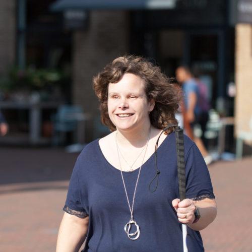 Marjolein op straat met haar geleidestok in haar hand