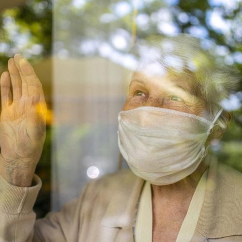 Oude vrouw met mondkapje, achter het raam