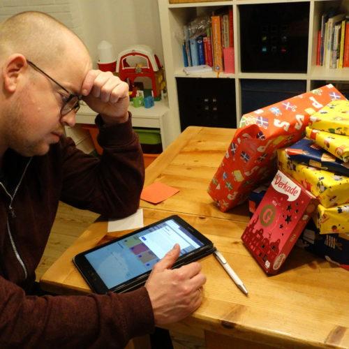 Wolter probeert op tablet online te bestellen, op tafel ligt een stapel sintcadeautjes