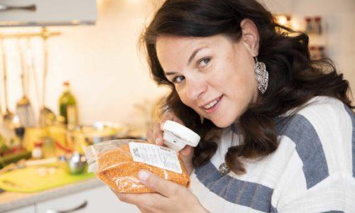 Annemiek in de keuken terwijl zij met een vergrootglas een verpakking leest